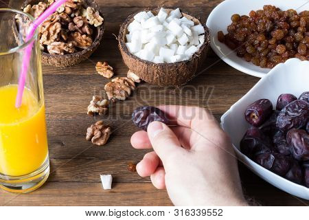 Healthy Food Eating Process. The Male Hand Holds A Date Fruit.