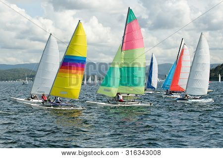 Children Sailing In Small Boats And Dinghies With Colourful Sails For Fun And Competition. Teamwork
