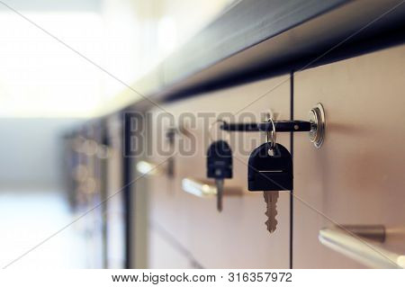 Close Up Key Locked On Filing Cabinet Drawer Desk Furniture In Office Building.