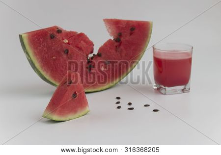 Slice Of Watermelon And A Glass Of Juice On A White Background.