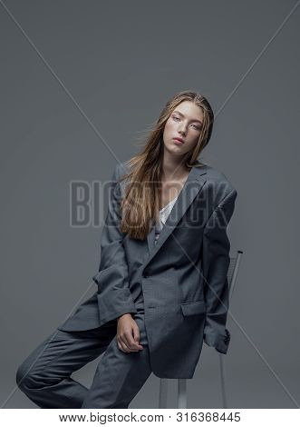 Portrait Of Weary Young Beautiful Woman In Oversized Mans Suit Sitting Isolated Grey Background