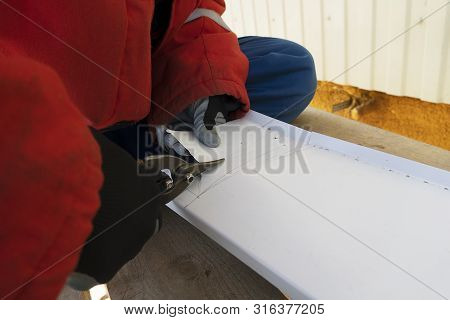 A Craftsman In Gloves Cuts A White Steel Sheet With Scissors. A Working Tinsmith Cuts Iron At A Mark