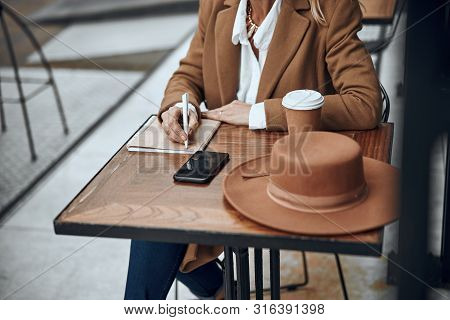 Lady At The Table Writing In Notebook Stock Photo