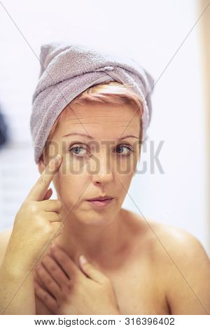 Young Girl Is Worried About The Wrinkles On Her Face. Anti-wrinkles Care Concept