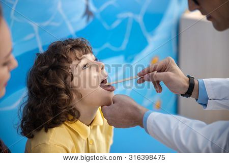 Doctor Is Examining Kid Throat In Office Stock Photo