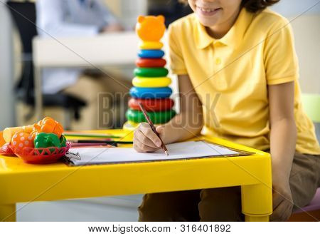 Joyful Kid Drawing In Clinic Stock Photo