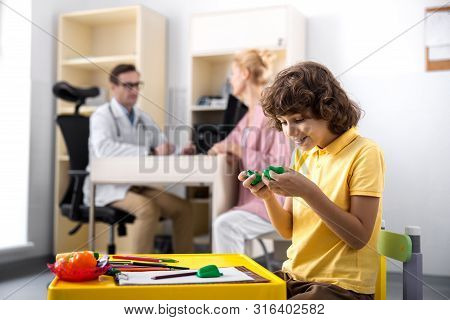 Joyful Boy Playing Games In Clinic Office Stock Photo
