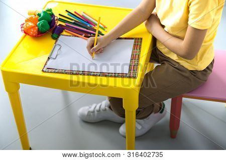 Child Is Drawing At Desk Stock Photo