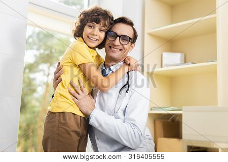 Pediatrician And Boy Enjoying Appointment In Hospital Stock Photo