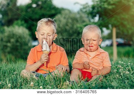 Two Caucasian Funny Children Boys Siblings Sitting Together Eating Sharing One Ice-cream. Toddler Yo