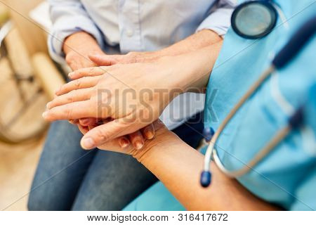 Nurse or nurse holds the hand of a senior citizen in the nursing home