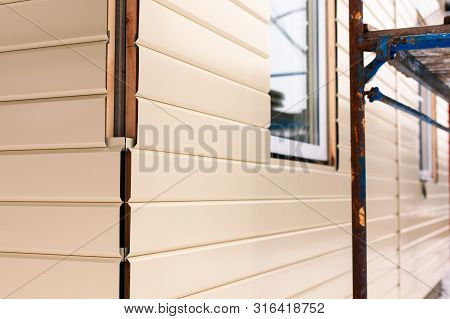House Corner With Beige Siding Covering The Walls And Scaffolding. Focus On Corner. Closeup.