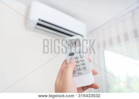 Hand With Remote Control Directed On Air Conditioner. Home Air Conditioning Concept
