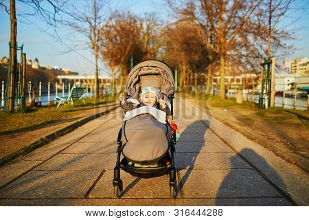 Adorable Happy Little Girl Sitting In Pushchair Outdoors On A Fall Or Spring Day On Swan Island On T