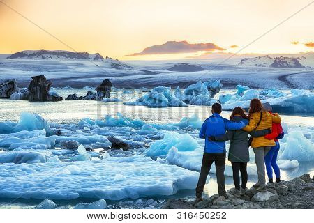 Group Of Tourist Looking Beautifull Landscape With Floating Icebergs In Jokulsarlon Glacier Lagoon A