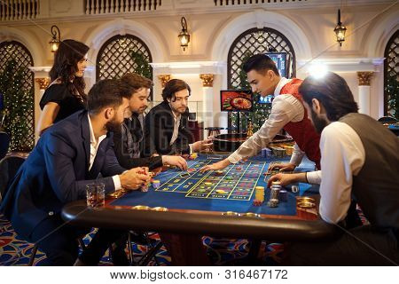 Poople Make Bets Gambiling At The Roulette Table In The Casino.