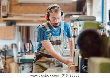Absorbed carpenter with ear protection and safety goggles at the milling machine working on wood