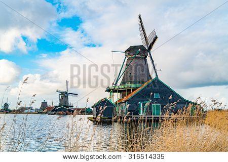 View Of Dutch Windmills Near The River Zaan In The Village Of Zaanse Schans, Netherlands