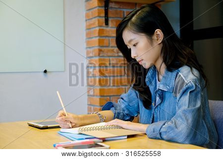 Asian Woman University Student In Casual Writing On Paper Notebook, Teenager Student Hand Writing Le
