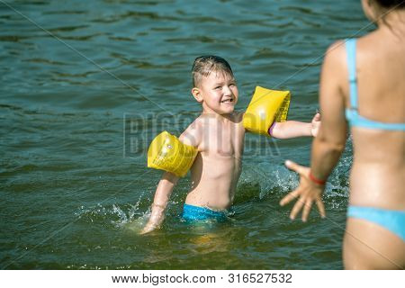 Little Toddler Boy With Inflatable Armbands Aids Playing In Water With Mother In Lake Water Summer V