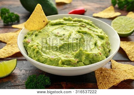 Bowl Of Fresh Guacamole With Nachos Chips And Herbs. Healthy Vegan, Vegetables Food