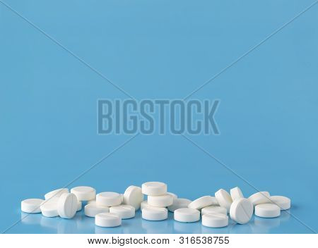 Heap Of Round White Pills. Blue Background With Text Space