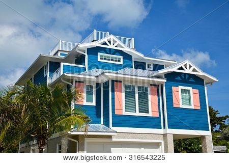 Large Beach House Painted In Dark Blue With White Trim And Coral Shutters. House Has Roof Deck, Gara