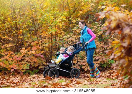 Family Hiking With Stroller In Autumn Park