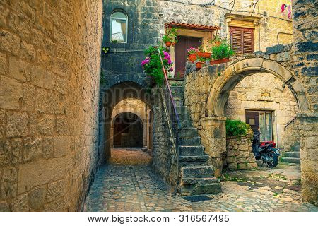 Picturesque Narrow Street With Stone Houses. Rustic Stone Houses And Entrances Decorated With Flower
