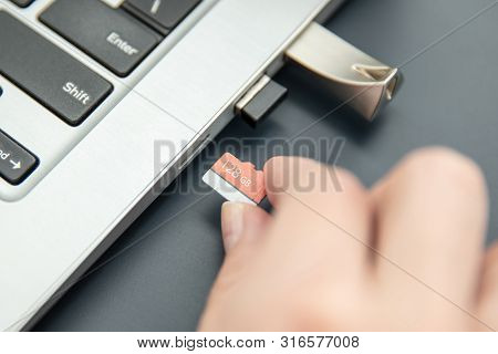 Woman's Hand Puts In Fast, Capacoius Microsd Card To The Modern Ultrabook.