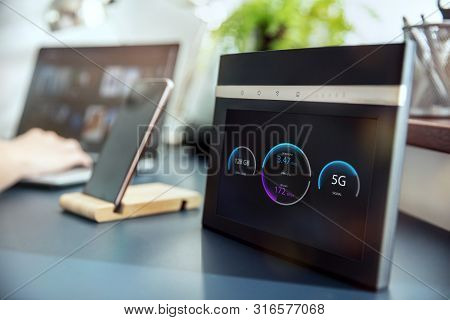 Modern 5g Wi-fi Router With Display On The Desk And Devices On The Background. Interface On The Scre
