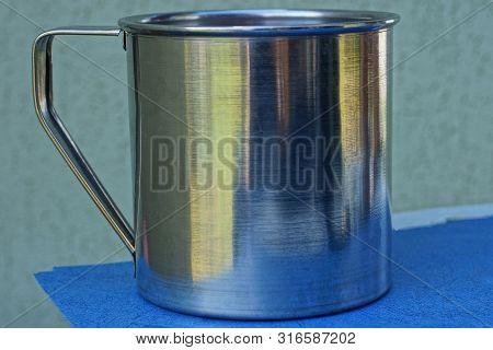 One Big Gray Metal Mug Stands On A Blue Table