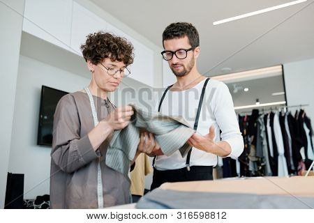 Young man and woman choosing textile for new fashion collection in studio