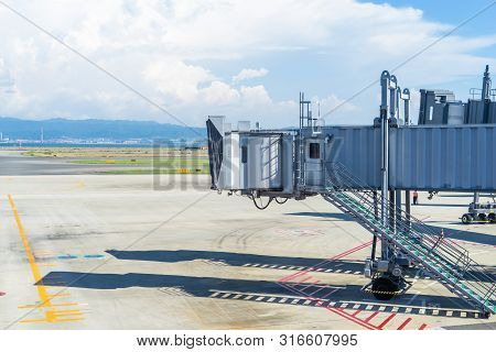 Empty Airport Passenger Bridge On Airport Runway Without Plane