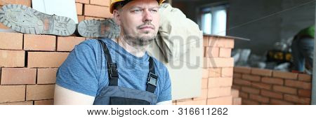 Portrait of bearded builder thinking about new project. Pensive constructor looking away thoughtfully. Professional holding plan folder and writing estimate. Building concept poster