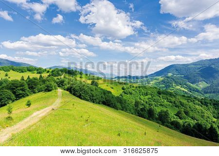 Beautiful Mountain Landscape In Summertime. Footpath Through Forests And Grassy Meadow On Rolling Hi