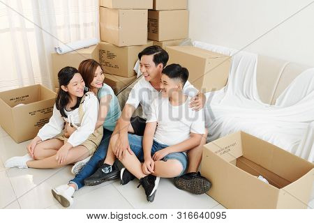 Happy Parents Hugging Their Teenage Kids When Resting On The Floor In Their New Apartment After Movi