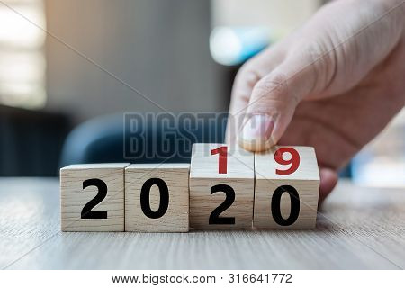 Business Man Hand Holding Wooden Cube With Flip Over Block 2019 To 2020 Word On Table Background. Re