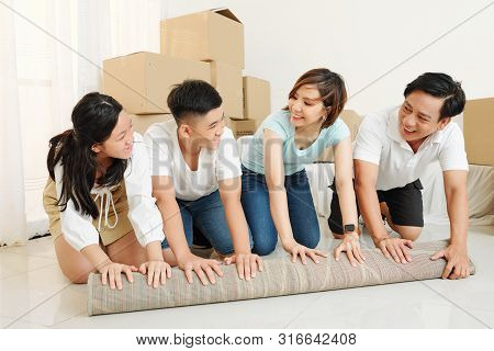 Happy Asian Family Of Four Unfolding Carpet And Looking At Each Other With Smiles On Faces