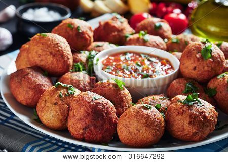 Close-up Of Deep Fried Plantain Fritters Klako On A White Plate With Hot Pepper And Tomato Sauce, Af