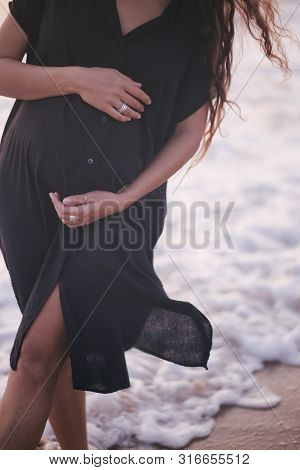 Beautiful Young Pregnant Woman With Long Curly Healthy Hair Wearing Black Dress Walking At The Beach