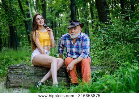 Person With Purported Magical Abilities. Pretty Woman And Senior Freak Grandpa. Woodman Magician Con