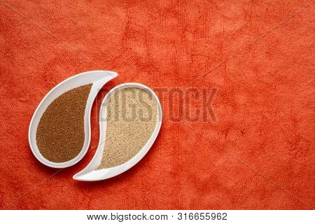 gluten free brown and ivory teff grain on teardrop shaped bowl against red  textured paper - important food grain in Ethiopia and Eritrea
