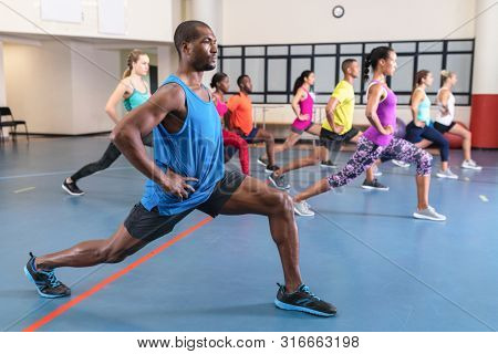 Side view of African-american male trainer training people to perform yoga in fitness center. Bright modern gym with fit healthy people working out and training