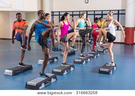 Side view of diverse female trainer training people to exercise on aerobic stepper in fitness center. Bright modern gym with fit healthy people working out and training