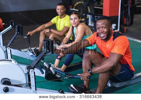 Portrait of diverse fit people exercising with rowing machine in fitness center. Bright modern gym with fit healthy people working out and training