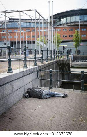 A Homeless Man Lying On The Street