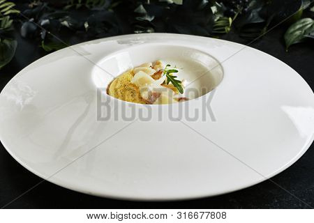Exquisite Serving White Restaurant Plate of Homemade Italian Cream Polenta with Porcini Mushrooms and Pecorino Cheese Close Up. Fine Italian Dish of Boiled Cornmeal on Natural Black Marble Background poster