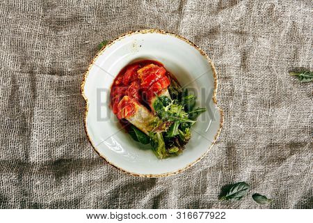 Fried Cheese, Sweet Pepper, Green Leaves of Lettuce and Arugula in Tomato Sauce Top View. Capsicum Peppers or Bell Peppers with Baked Edam or Gouda Topped with Leaf Salad in Round Plate