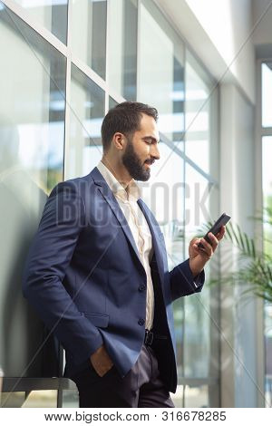 Delighted Bearded Businessman Leaning On Glass Wall